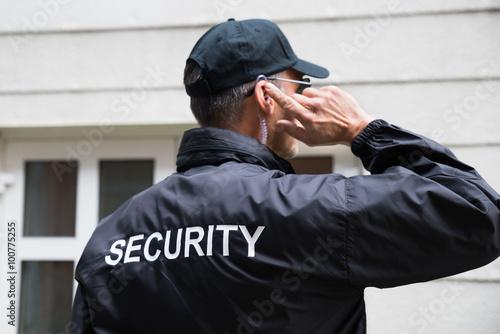 Fototapeta Security Guard Listening To Earpiece Against Building