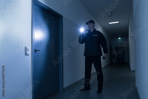 Security Guard With Flashlight Standing In Front Of Door Poster Mural XXL