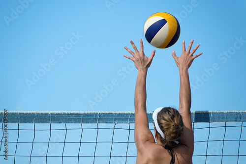 obraz lub plakat Beach volleyball player jumps on the net and tries to blocks the ball