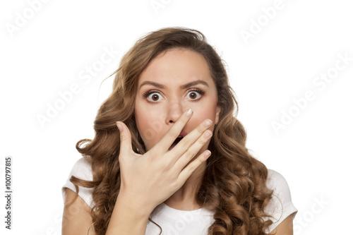 Leinwand Poster Schönes entsetztes Mädchen auf einem weißen Hintergrund