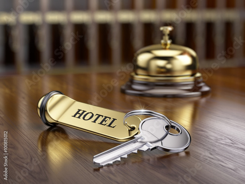 Hotel key and reception bell on reception desk