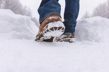 Man Walks With Boots Through Deep Snow In  Winter Day.