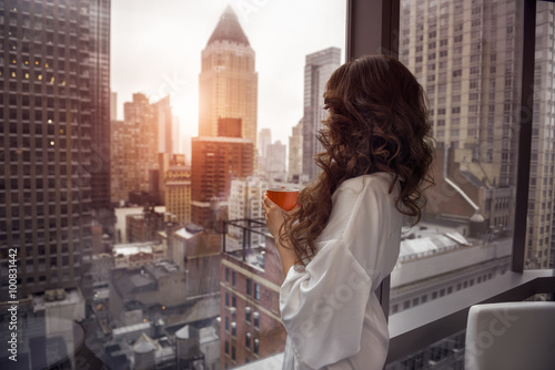 Obraz Beautiful woman holding coffee cup and looking to the window in luxury Manhattan penthouse apartments. Good morning after wake up. - fototapety do salonu