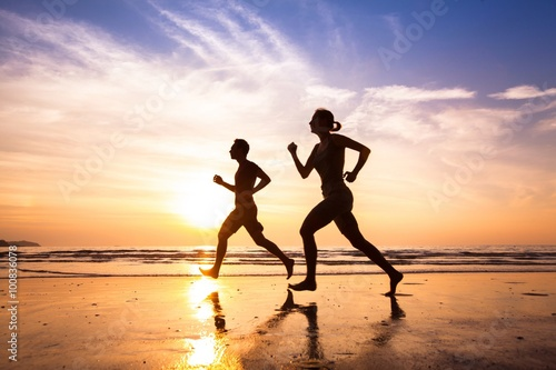 Fototapeta runners on the beach, sport and healthy lifestyle obraz