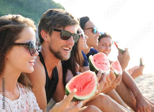 Fotografie, Tablou  Friends eating watermelon on beach
