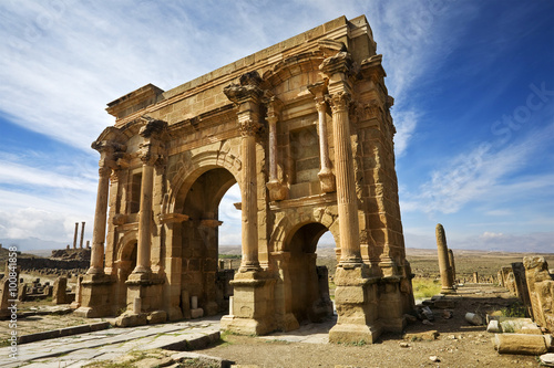 In de dag Algerije Algeria. Timgad (ancient Thamugadi or Thamugas). Triumphal arch, called Trajan's Arch and fragment of Decumanus Maximus street