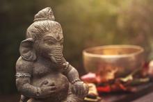 Ganesha Deity Stone Statue And Singing Bowl On The Background