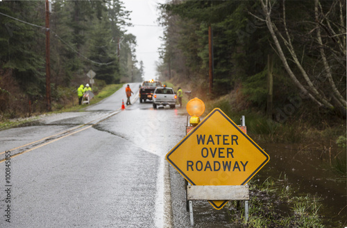 Valokuva Emergency workers placing warning signs on flooded road