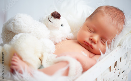 Photo  Cute newborn baby sleeps with toy teddy bear