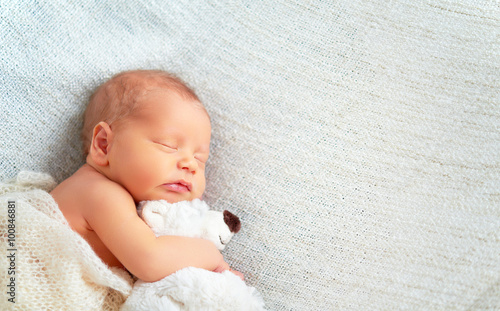 Fényképezés  Cute newborn baby sleeps with toy teddy bear
