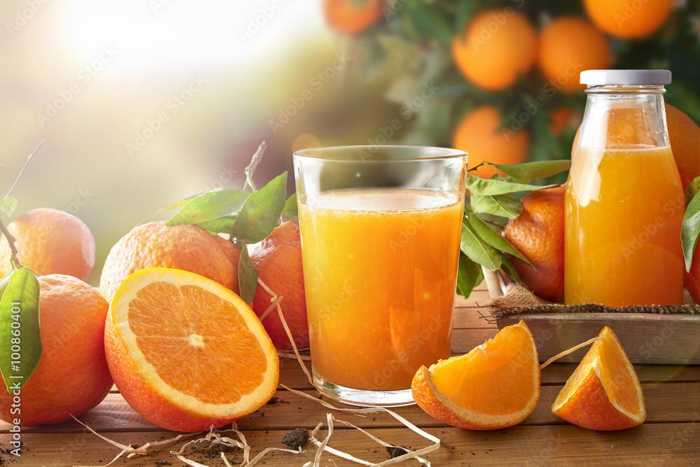 Fototapeta Glass of orange juice on a wooden in field