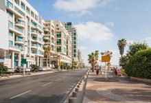 Highway Along Embankment With Buildings On Road Side, Parking And People Walking Along. Tel Aviv, Israel.
