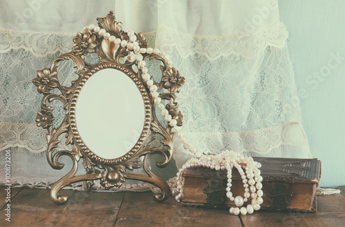 Obraz Antique blank Victorian style frame and old book with vintage pearl necklace on wooden table. retro filtered image. template, ready to put photography  - fototapety do salonu