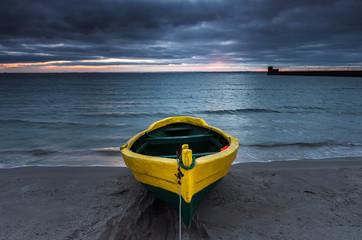 Fototapetałódź rybacka na brzegu plaży o zachodzie słońca