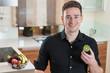 Junger Mann mit einer frischen Kiwi