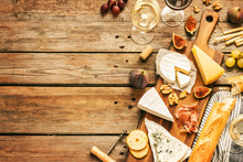 Different Kinds Of Cheeses, Wine, Baguettes, Fruits And Snacks On Rustic Wooden Table From Above. French Tasting Party Or Feast Scenery. Background Layout With Free Text Space.
