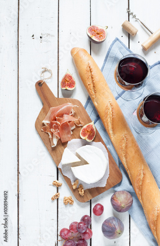 Spoed Foto op Canvas Picknick Camembert cheese, prosciutto (italian ham), baguette, two glasses of red wine, figs and grapes. White wooden table as background. Romantic french picnic scenery captured from above (top view).