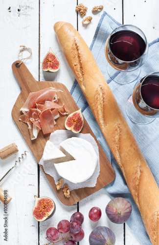 Keuken foto achterwand Picknick Camembert cheese, prosciutto (italian ham), baguette, two glasses of red wine, figs and grapes. White wooden table as background. Romantic french picnic scenery captured from above (top view).