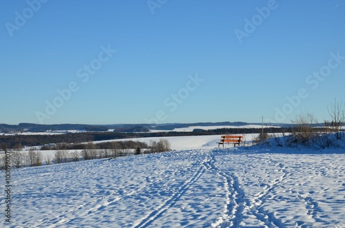 Foto op Plexiglas Arctica Holzbank in winterlicher Hügellandschaft