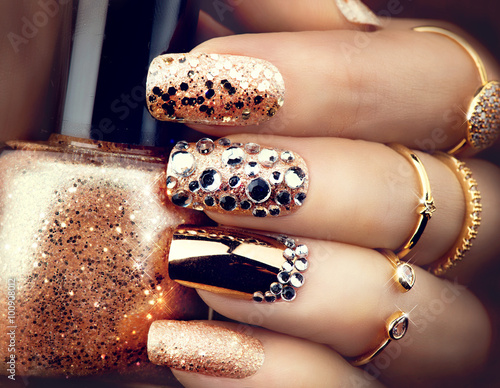 Staande foto Manicure Golden holiday style bright manicure with gems and sparkles. Trendy accessories