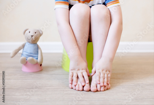 Photo closeup of legs of the child sitting on the potty