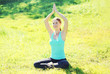 Young woman doing yoga exercises sitting on grass in sunny summe
