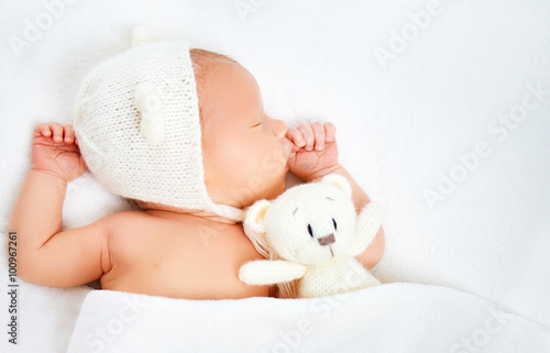 Photo  Cute newborn baby in bear hat sleeps with toy teddy bear