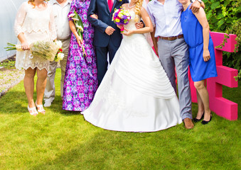 Wedding couple posing with guests. Summer newlyweds photo