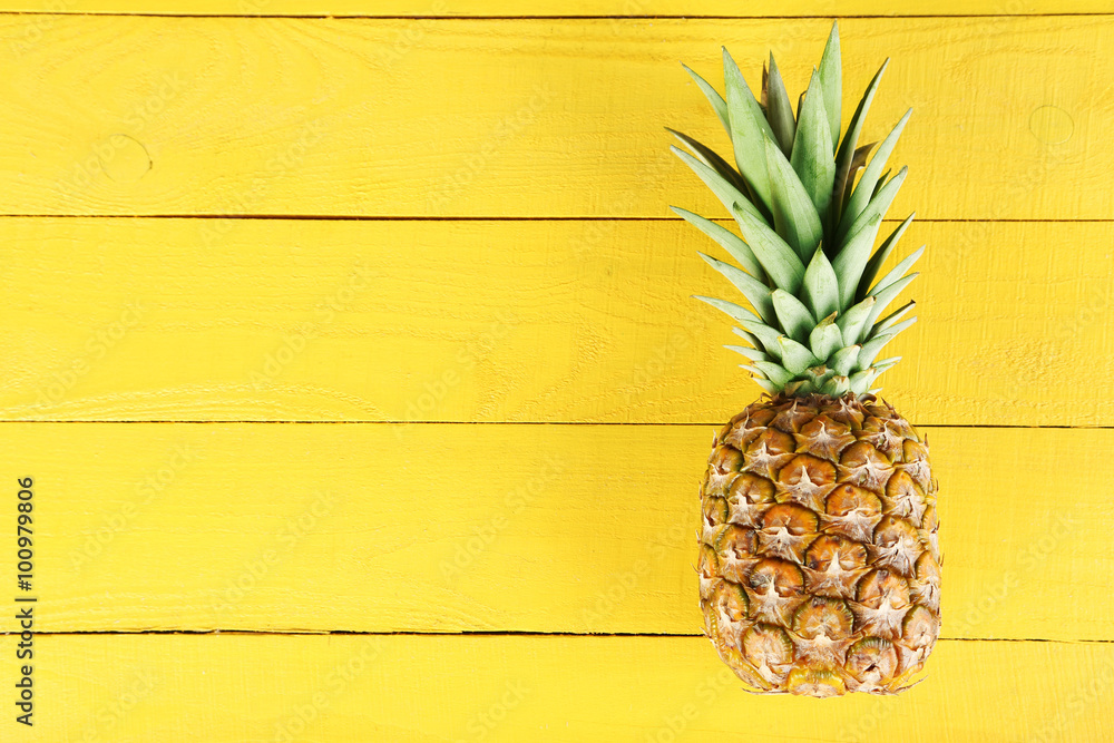 Fototapeta Ripe pineapple on a yellow wooden background