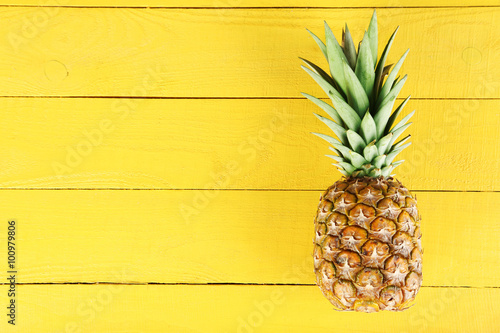 Ripe pineapple on a yellow wooden background Wallpaper Mural