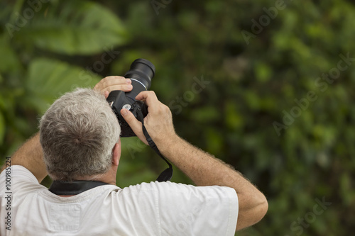 Photo  Male photographer captures a bird photo in the rain forest