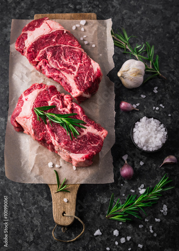 Photo  Two raw fresh marbled meat black angus steak ribeye, garlic, salt and  on dark b