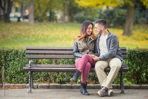 Fotografia  Happy young couple in love sitting on a park bench