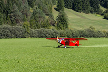 Light Red Aircraft Landing On A Green Meadow, Transportation, Outdoor