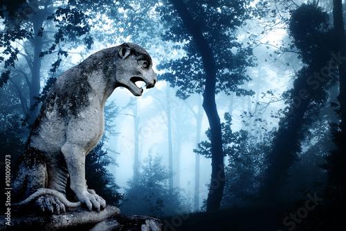 Fotografie, Tablou Ancient lion statue in misty forest