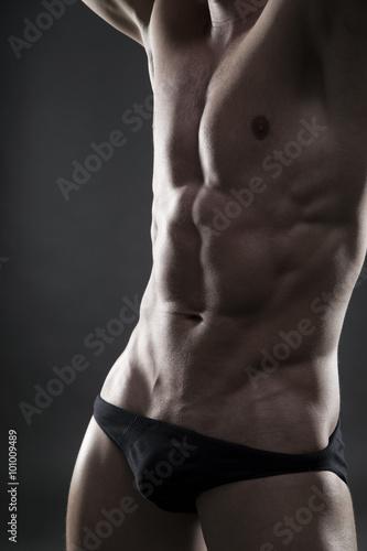 Fototapety, obrazy: Handsome muscular bodybuilder posing on gray background. Low key close up studio shot