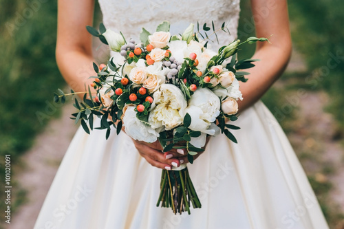 Foto  bride holding a bouquet of flowers in a rustic style, wedding bouquet
