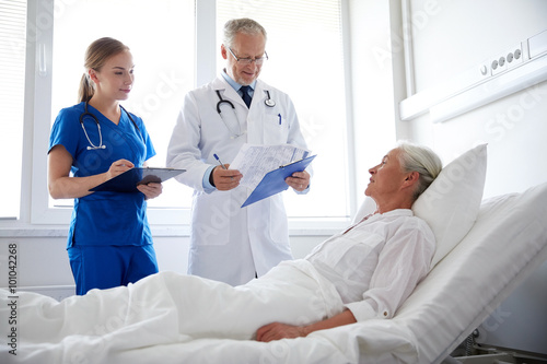 doctor and nurse visiting senior woman at hospital Poster