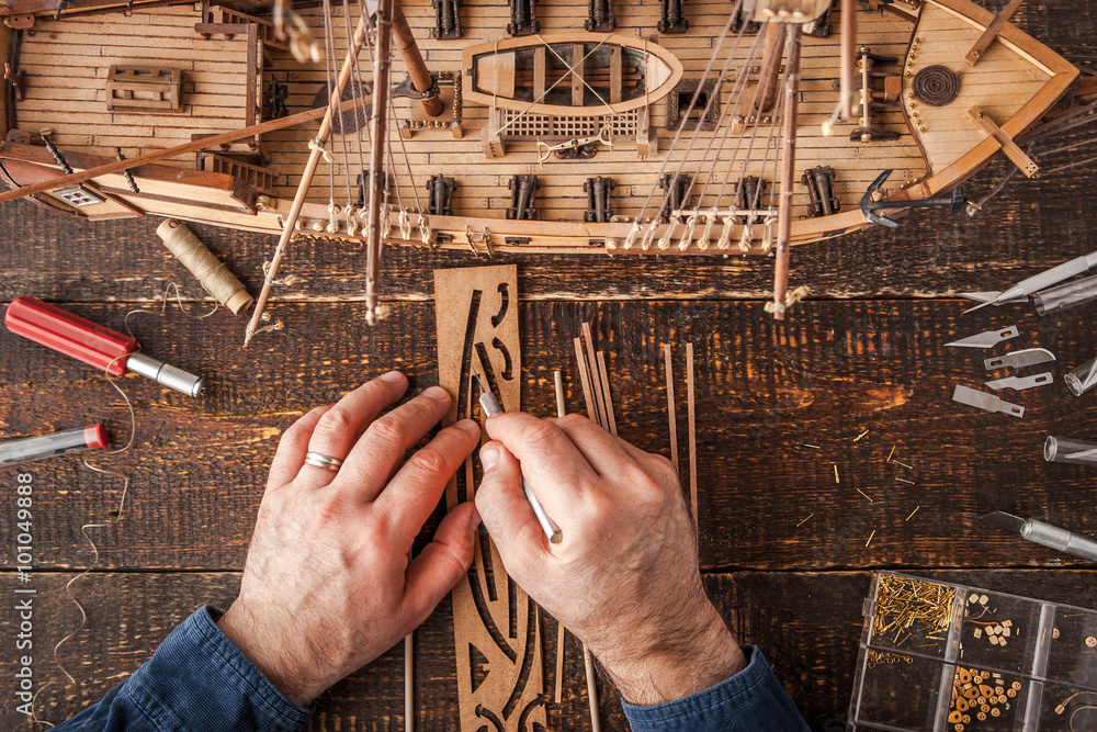 Fototapety, obrazy: Man collects the vehicle model on the wooden table