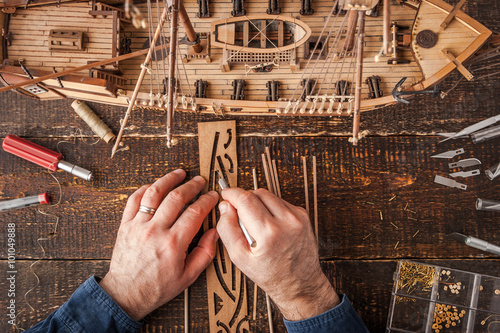 Photo  Man collects the vehicle model on the wooden table