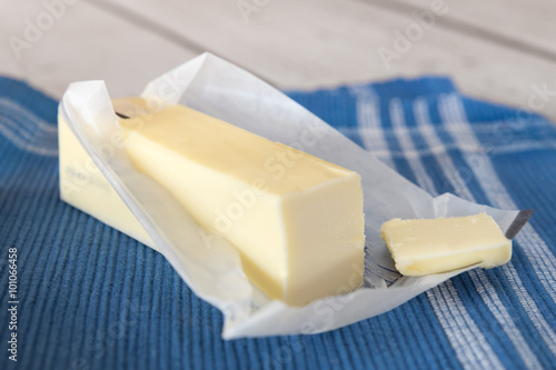 Fotografia, Obraz  Stick of unwrapped butter on blue cloth