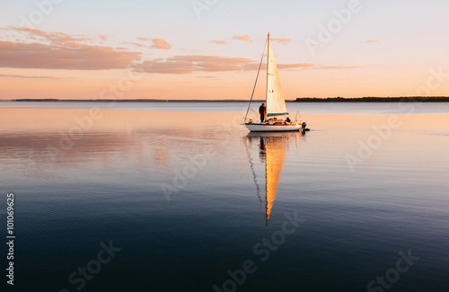 Sailing boat on a calm lake with reflection in the water Fototapeta