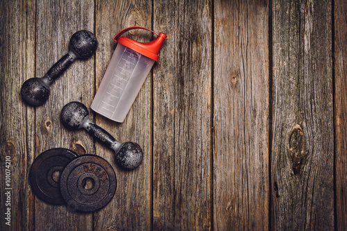 Fotografia  Old iron dumbbells and shaker on an old wooden table