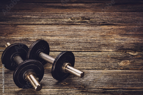 Fotografia  Old iron dumbbells on an old wooden table