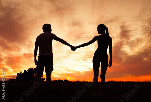 Fotografie, Obraz  Couple holding hands in the sunset.