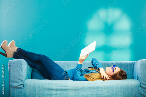 Fotografie, Obraz  woman with tablet relaxing on couch blue color