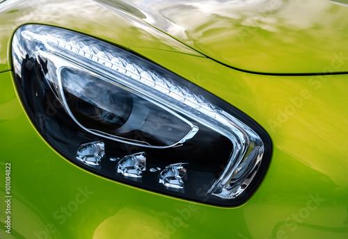 Fototapeta Closeup headlights of modern sport green car. Car exterior detail. obraz na płótnie
