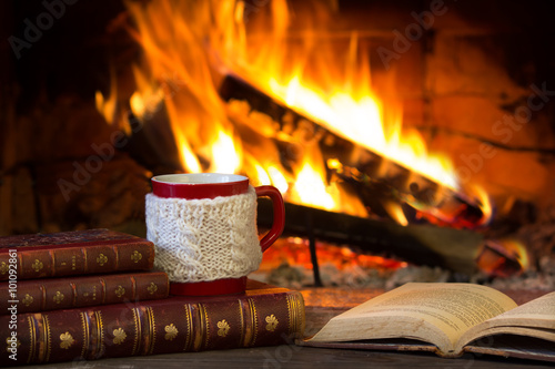 In de dag Chocolade Cup of hot drink and antique books in front of warm fireplace. Red mug in white knitted mitten standing near fire. Magical relazed cozi atmosphere.