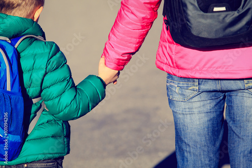 Fotografia, Obraz  Mother holding hand of little son with backpack on the road