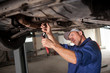 Portrait of auto mechanic working with tools under car in automo